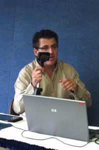 WTOP reporter Neal Augenstein demonstrates a gerry-rigged mic clip for the iPhone, using a traditional mic clamp and a scrap of foam to wrap around the phone.